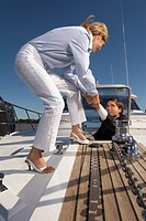 Woman helping man onto deck of boat