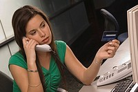 Businesswoman on the phone with credit card in hand