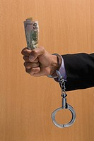 Detail of businessman's handcuffed hand holding cash