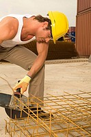 Male construction worker cutting iron rods with a grinder