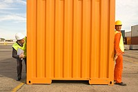 Male dock worker hiding from a businessman behind a cargo container at a commercial dock