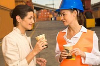 Two businesswomen holding disposable cups and talking