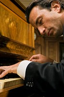 Close_up of a young man playing a piano