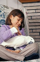 Little girl pets her loving umbrella cockatoo Cacatua alba.