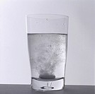 A tablet dissolving in a glass of water