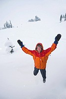 Man in Orange Jacket jumping in air, Quebec, Canada.