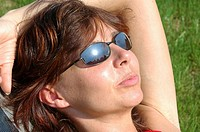 woman with sunglasses basks in sun