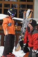 A father helps his son with his skis and bindings, Whistler Mountain, British Columbia, Canada.