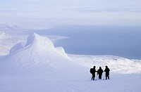 Three persons standing in a snow covered area