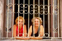 Two friends smile at the photographer through the bars of a window, Havana, Cuba.