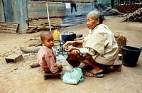 Grandson and Grandmother cooking around a fire in Ban Phanom, Laos.