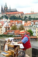 Colorful vendor with syncopator music on the famous Charles Bridge in Prague, Czech Republic.
