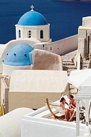 Couple on Terrace and Blue Domes of a Greek Orthodox Church, Oia, Santorini, Cyclades Islands, Greece