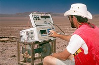 Geologist reading conductivity tests for mineral deposits, Atacama Desert, Chile.