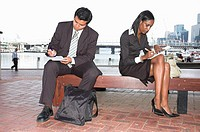 Young businesspeople filling in paperwork while working out of the office