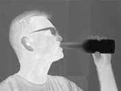 Thermogram of a man drinking a beer. The different shades represent different temperatures. The lightest shades are the hottest temperatures, while th...