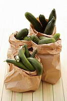 Various types of cucumbers in paper bags