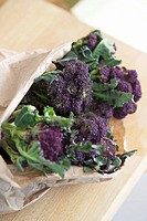 Purple sprouting broccoli with leaves in a paper bag
