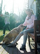 Young woman stroking dog with her friend exercising in background