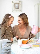 Girl and her mother smiling at breakfast table
