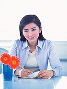 Image of a Business Woman Working at her Desk, Next to Some Orange_colored Flowers, Front View, Looking at Camera, Smiling