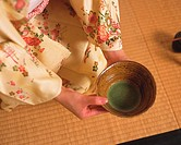 Woman in kimono holding a tea cup at tea ceremony, high angle view, Japan