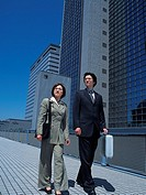 Businessman and businesswoman looking away by the high rise building, Low Angle View