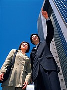 Businessman and businesswoman pointing and looking at something by the high rise building, Low Angle View