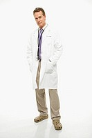 Studio shot of a mid-adult Caucasian male doctor with hands in lab coat pockets.