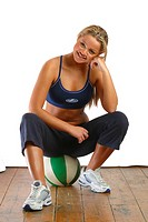 Athletic blonde in workout gear sits on ball