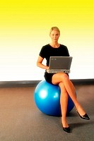 Professional woman sitting on a fitness ball and using her laptop