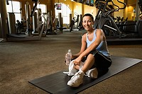 Adult Caucasian female sitting on mat on gym floor (thumbnail)