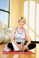 Mature Caucasian female adult sitting on mat at gym