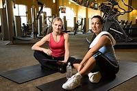 Adult Caucasian female with personal trainer at gym