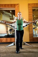 Adult Caucasian female using exercise equipment at gym