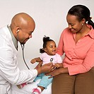 African_American male doctor examining baby girl with mother watching