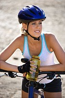 Caucasian mid_adult woman wearing bicycle helmet, sitting on bicycle, holding water bottle