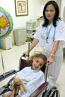 Portrait of nurse pushing young patient in wheelchair