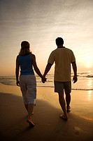 Caucasian mid_adult couple walking holding hands on beach at sunset