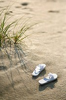 Two white sandals on sandy beach (thumbnail)
