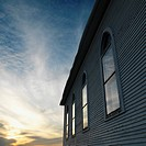 Sunset and clouds behind side view of building with arched windows and wooden siding