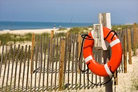 Life preserver hanging on post on beach on Bald Head Island, North Carolina