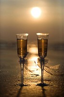 Pair of flute glasses filled with champagne with bows on stems on beach at sunset