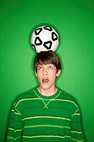Portrait of Caucasian teen boy balancing soccer ball on head and looking up at it with eyes.