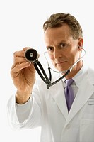 Studio shot of a mid_adult Caucasian male doctor holding out stethoscope.