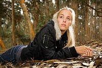 Young adult Caucasian woman lying on ground in forest (thumbnail)