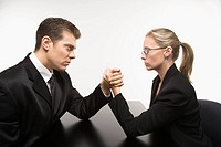 Side view of Caucasian mid_adult businessman and businesswoman arm wrestling on table.