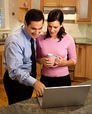 Mid_adult couple looking at laptop computer while standing in kitchen.