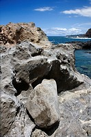 Close_up of rocky shoreline with ocean and blue sky in Maui, Hawaii