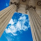 Low angle view looking up at blue sky with clouds and columns of Supreme Court building in Washington D.C